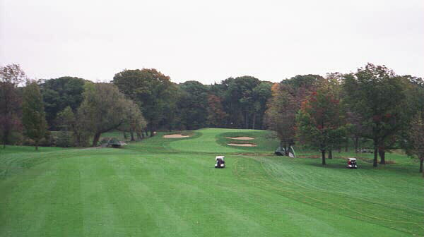 After a blind drive over a hill, the golfer is faced with a long approach to an elevated green that is well defended.