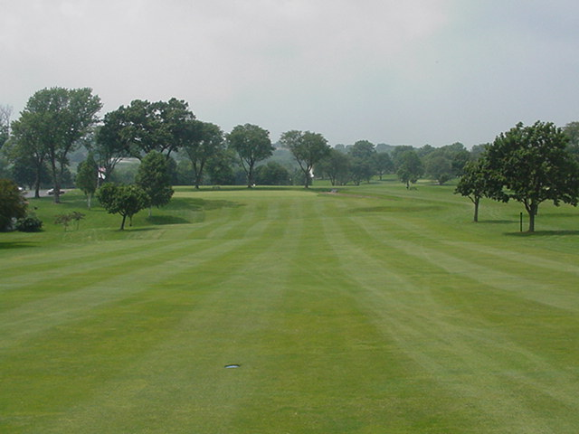 Tee shots on the closing hole should be down the right to stay in the fairway. The putting green is protected by the trees on the left.