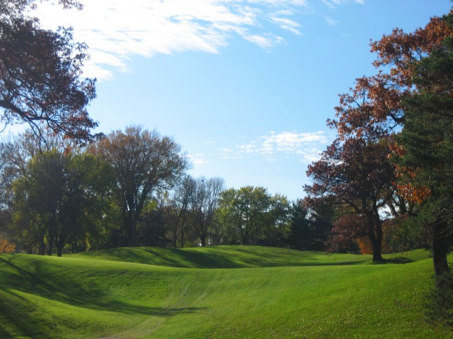 Tee shot on the thirteenth. The shaded area to the left is fairway making it larger than it appears in this picture. The crest of the hill is about 200 yards from the tee. A flat spot 80 yards from the green can be reached by any shot that clears that crest within the confines of the fairway. Alternately, a good tee shot can carry the trees on the right.