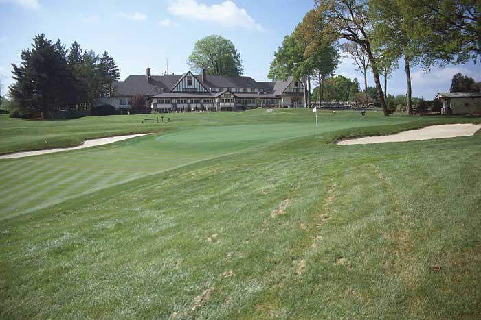 Approach shots that hit into the slight crown fronting the green will not advance towards the hole. The stately clubhouse looks over the 9th green and the 10th tee.