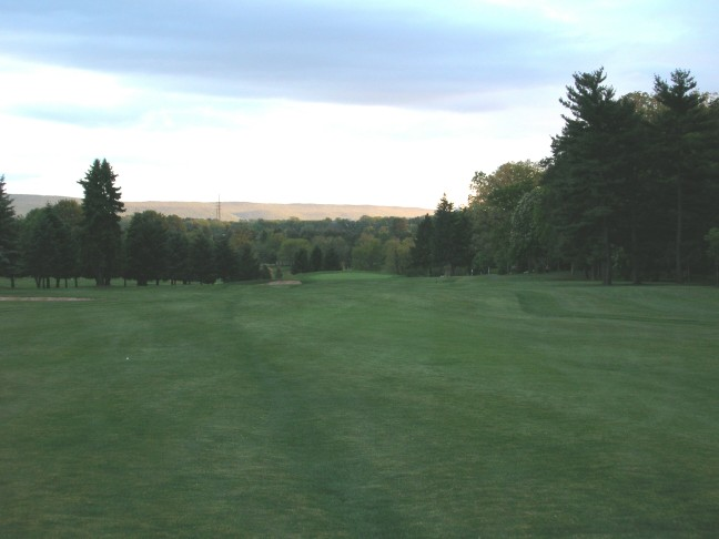 The long thirteenth hole at dusk, showing how much size the greens have lost. The original green stretched out to the edges of the green pad, which drops off twenty feet over the back and left.