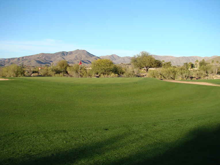 Short grass around the greens plays a prominent role at Desert Forest. This tightly mown bank back left of the third green is indicative of the type recovery shot that a golfer can expect should he miss greens.
