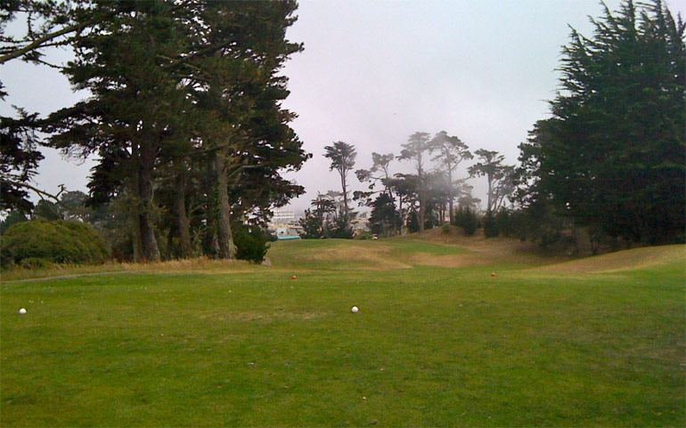 The 11th hole from the tee. The green is just to the left of the green roof in the distance.