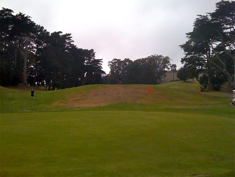 From behind the green, note the size of the 11th hole's mound relative to the size of the golfers on and to the left of it.