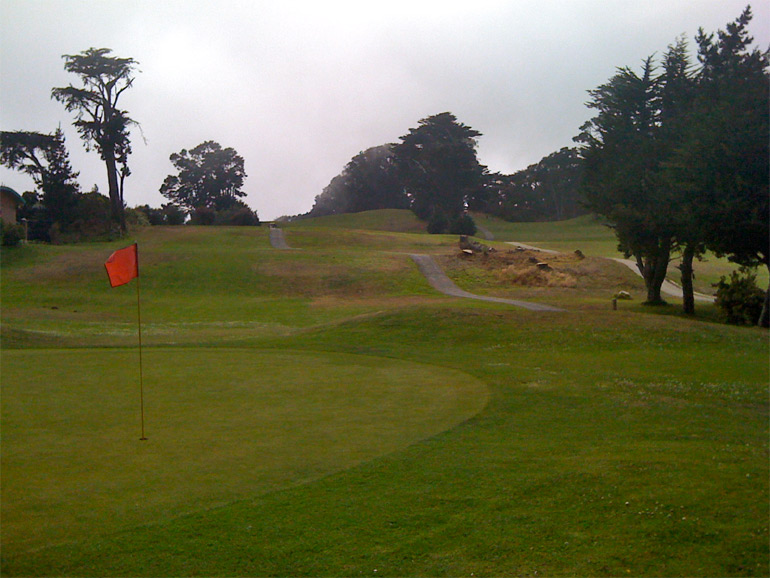 The 8th green in the foreground, 7th fairway upper-middle, and 9th fairway going uphill towards the trees top-right.
