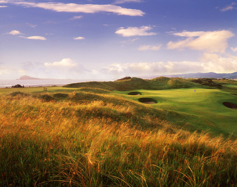 The great 12th green at Portmarnock nestles into the dunes. Its false front sends many a tee ball off the putting surface while its small but deep bunkers met out a different form of punishment. Certainly one of the great par 3s in world golf.