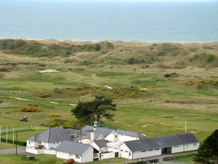 As seen from Harlech Castle, Royal St. David's clubhouse is in the foreground followed by its scintillating closing stretch of holes in the dunes. The golfer in red battles down the roly-poly fourteenth.