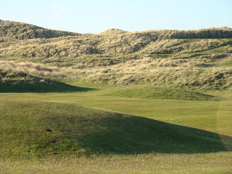 This view from across the course of the fourteenth tee areas benched into dune gives a sense of how much the fourteenth falls from tee to green. Controlling one's tee ball from a perched tee is never easy in a windy environment like Scotland.