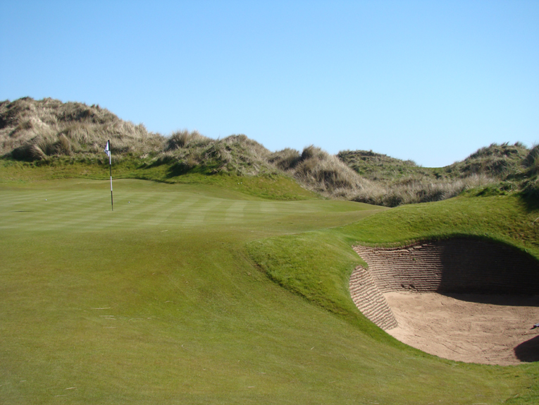 The bunkers are true hazards. Their steep revetted walls coupled with small concave floors conspire to make recovery difficult. Sometimes, play in the direction of the flag is not an option.
