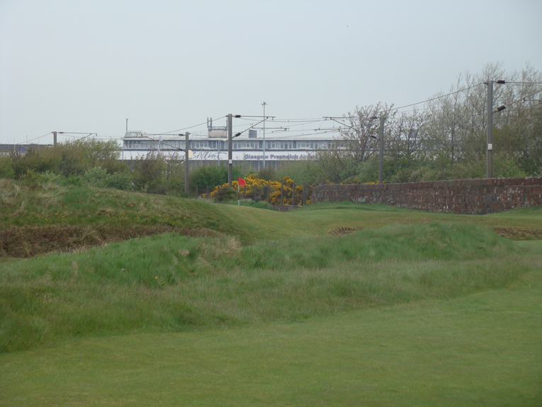 The natural tendency is to shy away from the wall with one's tee ball but that leaves a crummy view of the first green.