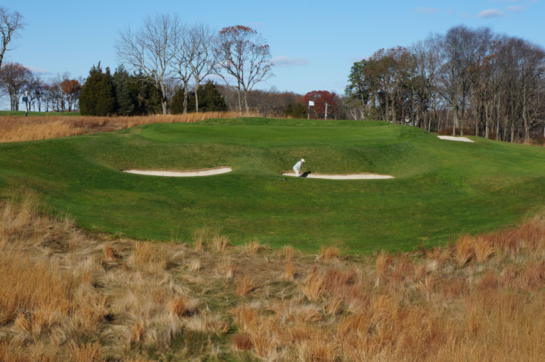 The golfer provides a sense of scale to the nasty pits that front the seventeenth green. One also gains a sense of the wicked nine yard long false front. If the golfer in the bunker doesn't carry his recovery shot at least twenty yards, he will likely get another chance.