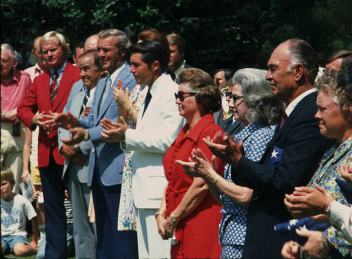 Chris's brother Henry is in the blonde in the white shirt bottom left. Chris is in the striped shirt behind Nicklaus. Snead's bald head is above Sarazen with Nelson just right of the frame. And, let's not forget Patty Berg on Hogan's left.