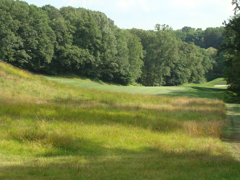Job 1 is to find the fairway. A fifty foot - no kidding - granite cliff looms right of fairway, so plenty of golfers shy away and use the hard left to right slope to kick their ball down the fairway.