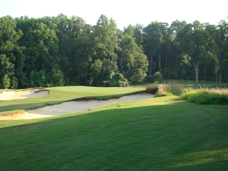 This newly created Coore bunker is actually thirty yards shy of the putting surface and creates a dead area from the tee. While tricky, the golfer who judges the distance properly sees his tee ball tumble onto the open green.