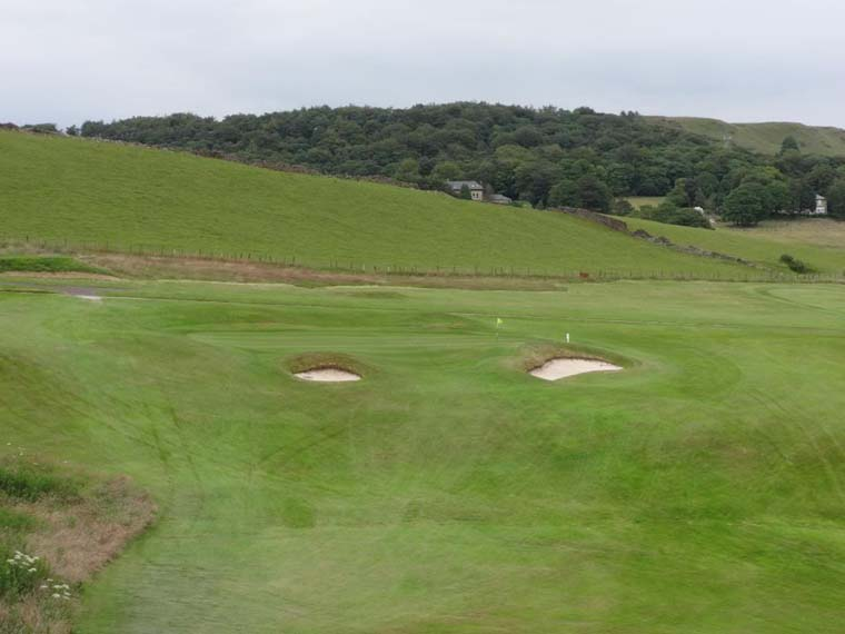 The pitch of the green pushes balls back down the hill toward the front bunkers. Any approach landing halfway up the slope of the green will do well to stay on the dance floor.